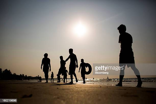Domestic tourists are silhouetted against the sun as they walk on the beach in Chaung Tha Myanmar on Saturday Jan 19 2013 Myanmar cleared about $1...