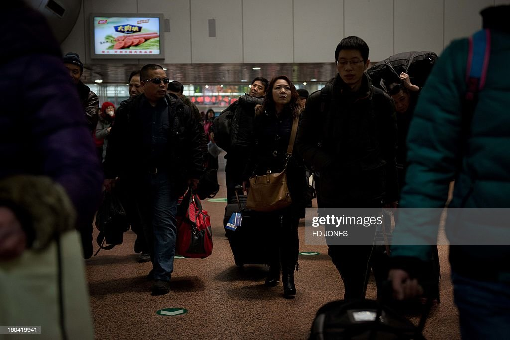 Domestic worker Chen Guolan (C) arrives at the Beijing West Railway Station to catch a train bound for the south-western Chinese city of Chongqing, a journey of 32 hours, and where she will also take another train for a further 6 hours to reach her home in Yiban, Sichuan province, early on January 31, 2013. The world's largest annual migration is underway in China with tens of thousands in the capital boarding trains to journey home for Lunar New Year celebrations. Passengers will log 220 million train rides during the 40-day travel season as they criss-cross the country to celebrate with their families on February 10, but just as making the trip home can be laborious -- often lasting one or two days -- so can simply acquiring a seat on the train, and every year complaints arise about the inefficiency or unfairness of the system, although an initiative allowing travelers to purchase tickets online aims to curb long queuing times. AFP PHOTO / Ed Jones