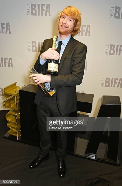 Domhnall Gleeson accepting the Best Supporting Actor award on behalf of his father Brendan Gleeson for 'Suffragett' poses at the Moet British...