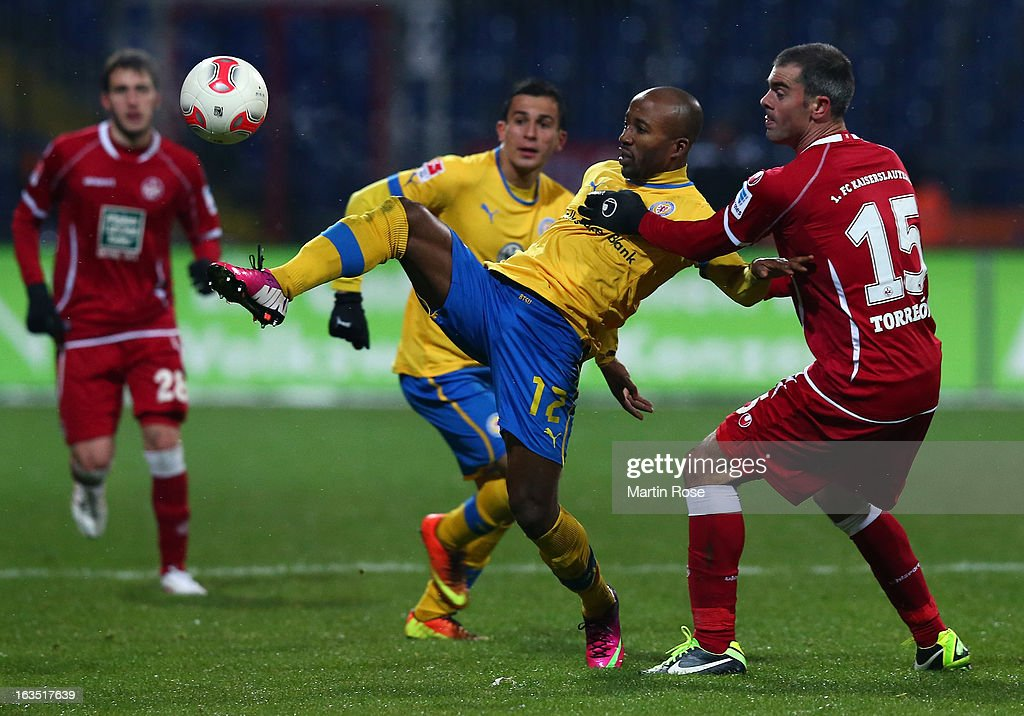 Domi Kumbela (L) of Braunschweig and Marc Tojerron (R) of Kaiserslautern battle for the ball during the second Bundesliga match between Eintracht Braunschweig and 1. FC Kaiserslautern at Eintracht Stadium on March 11, 2013 in Braunschweig, Germany.