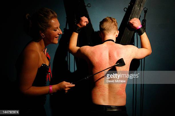 Domina beats a submissive man at a dungeon party during the DomConLA convention in the early morning hours of May 19 2012 in Los Angeles California...