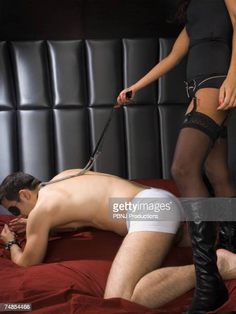 dominatrix holding leash around man's neck - women dominating men stock photos and pictures
