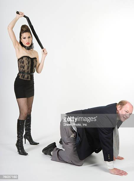 dominatrix preparing to whip businessman, studio shot - women whipping men stock photos and pictures