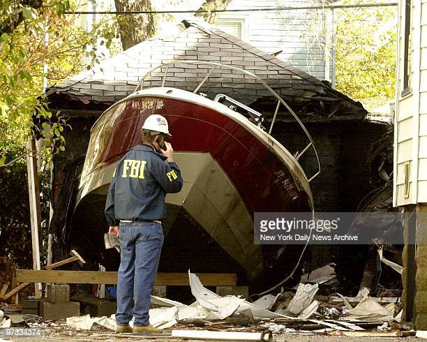 Domincan airliner flight 587 crashed in Rockaway after take-off from Kennedy Airport this morning. FBI investigator looks over boat that was hit with...