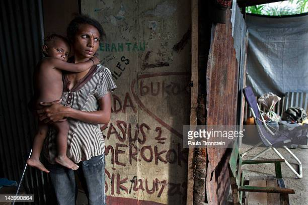 Domingas holds Tinan 18 months outside their small shack April 21 2012 in Dili East Timor Millions have been spent on aid during the first 10 years...