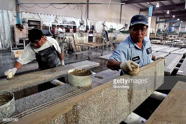 Domingo Gomez right rubs grout into precast terrazzo fauxmarble stair treads at the Precast Terrazzo Enterprises Inc manufacturing facility in...