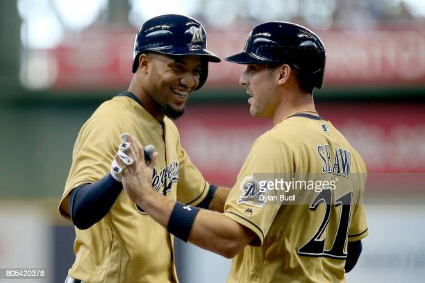 Domingo Santana and Travis Shaw of the Milwaukee Brewers celebrate after Santana hit a home run in the second inning against the Miami Marlins at...