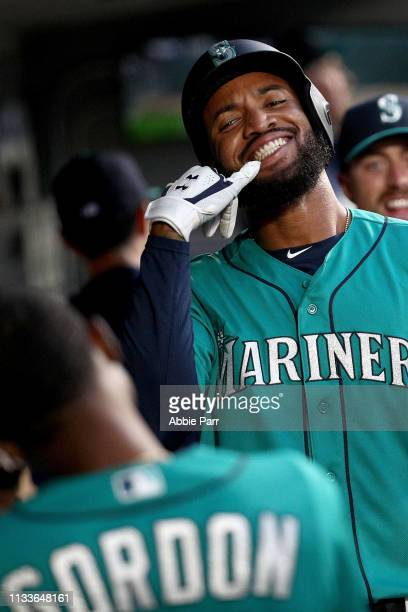 Domingo Santana celebrates with Dee Gordon of the Seattle Mariners after hitting a solo home run against the Boston Red Sox in the first inning...
