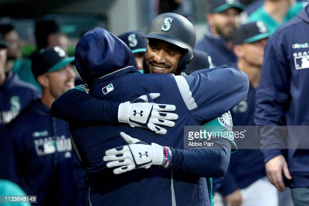 Domingo Santana hugs Felix Hernandez of the Seattle Mariners after hitting a solo home run against the Boston Red Sox in the first inning during...