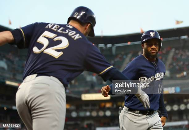 Domingo Santana is congratulated by Jimmy Nelson of the Milwaukee Brewers after he scored in the second inning against the San Francisco Giants at...