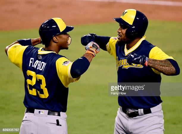 Domingo Santana of the Milwaukee Brewers celebrates his solo homerun with Keon Broxton to take a 10 lead over the Los Angeles Dodgers during the...
