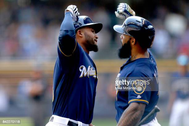 Domingo Santana of the Milwaukee Brewers celebrates with Eric Thames after hitting a solo homer during the second inning against the Washington...