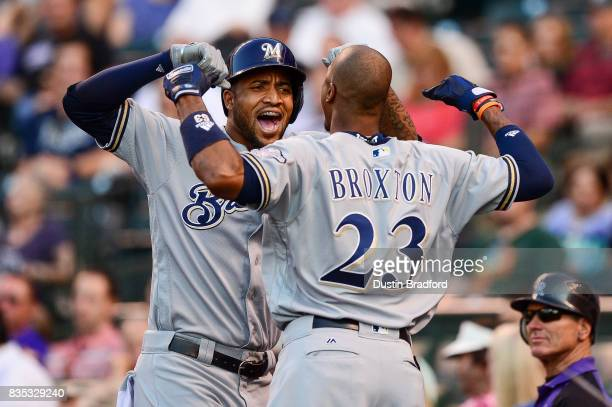 Domingo Santana of the Milwaukee Brewers celebrates with Keon Broxton after hitting a second inning solo homerun hit against the Colorado Rockies at...