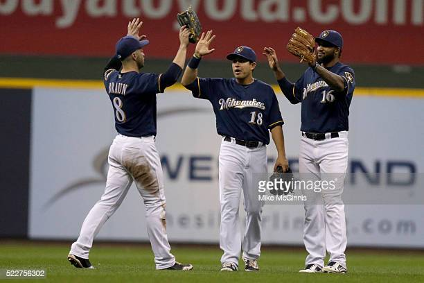 Domingo Santana of the Milwaukee Brewers celebrates with Ramon Flores and Ryan Braun after the 10-5 win over the Minnesota Twins at Miller Park on...