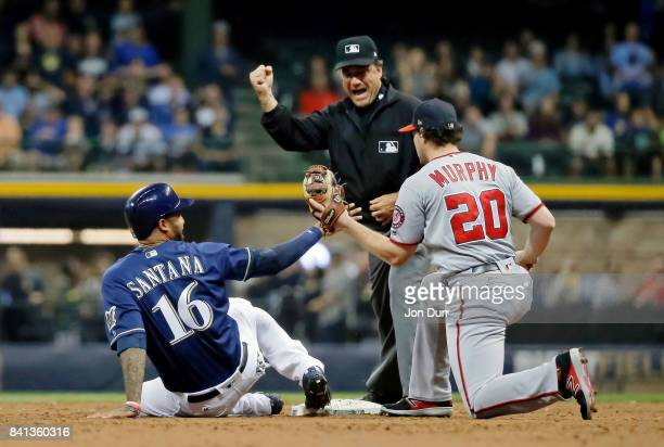 Domingo Santana of the Milwaukee Brewers is called out at second base by umpire Phil Cuzzi after being tagged out by Daniel Murphy of the Washington...