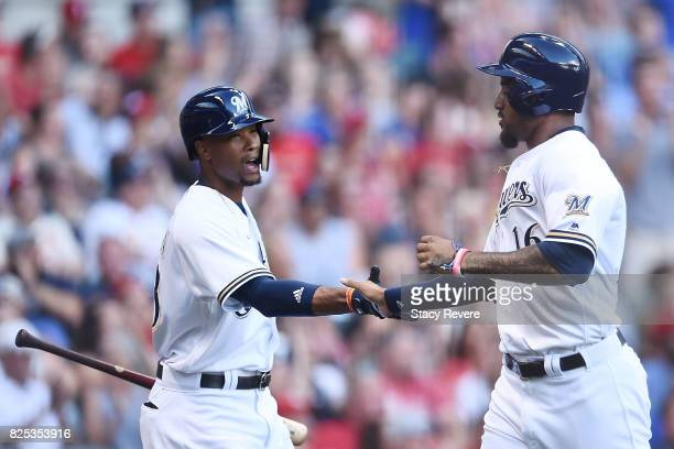 Domingo Santana of the Milwaukee Brewers is congratulated by Keon Broxton after scoring during the first inning against the St Louis Cardinals at...