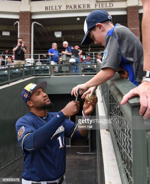 Domingo Santana of the Milwaukee Brewers signs autographs prior to a spring training game against the Kansas City Royals at Surprise Stadium on March...