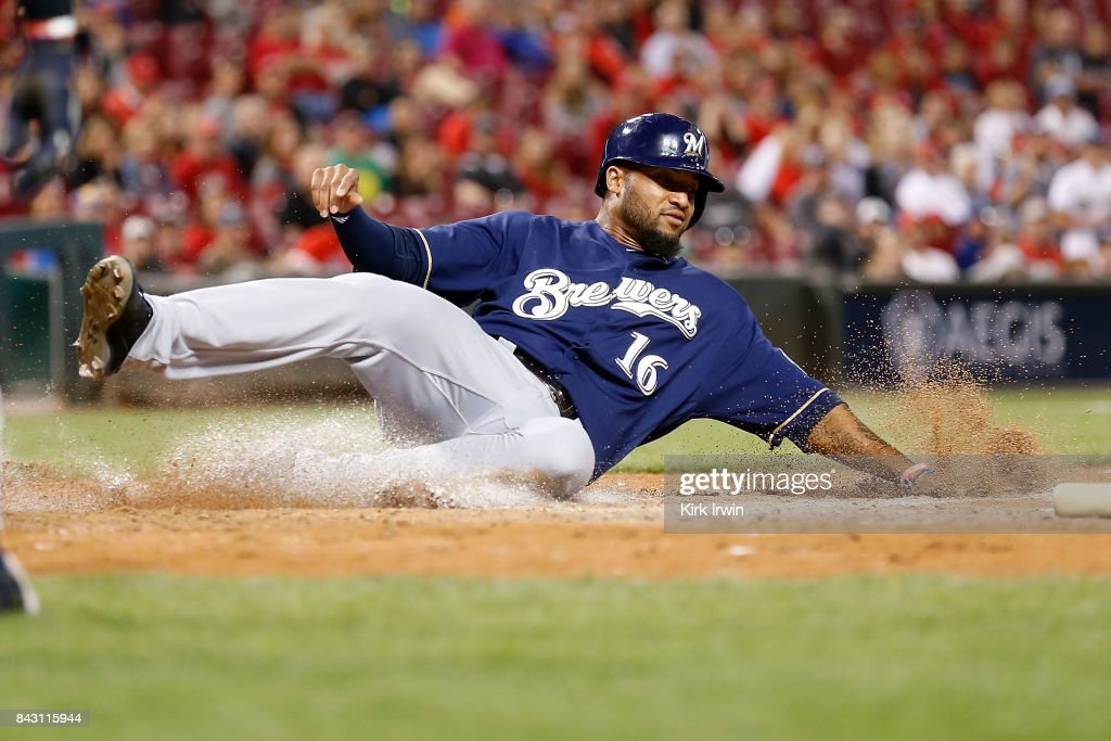 Domingo Santana #16 of the Milwaukee Brewers slides into home plate to score a run during the seventh inning of the game against the Cincinnati Reds at Great American Ball Park on September 5, 2017 in Cincinnati, Ohio. Cincinnati defeated Milwuakee 9-3.