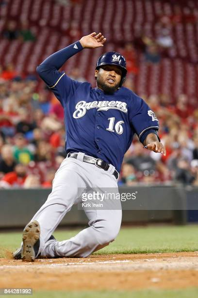 Domingo Santana of the Milwaukee Brewers slides into home plate to score a run during the game against the Cincinnati Reds at Great American Ball...