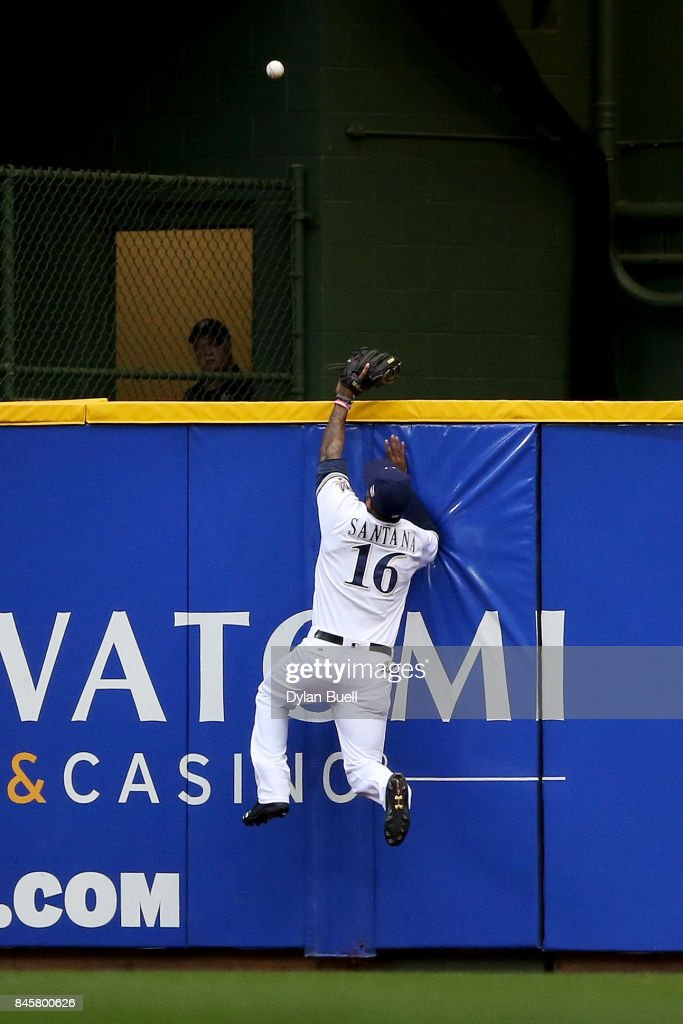 Domingo Santana #16 of the Milwaukee Brewers watches as a ball hit by Andrew McCutchen #22 of the Pittsburgh Pirates flies over the fence for a home run in the first inning at Miller Park on September 11, 2017 in Milwaukee, Wisconsin.