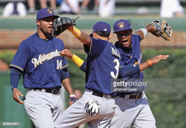 Domingo Santana Orlando Arcia and Keon Broxton of the Milwaukee Brewers celebrate a win over the Chicago Cubs at Wrigley Field on July 6 2017 in...