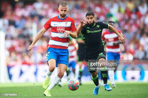 Domingos Duarte of Granada CF is followed by Nabil Fekir of Real Betis Balompie during the Liga match between Granada CF and Real Betis Balompie at...
