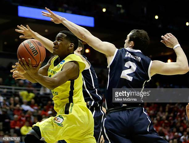 Dominic Artis of the Oregon Ducks drives to the basket as Matt Carlino of the Brigham Young Cougars defends during the second round game of the NCAA...