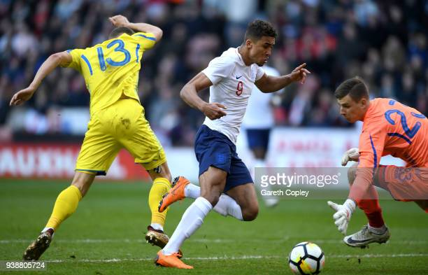 Dominic CalvertLewin of England scores the opening goal past Andriy Lunin of Ukraine during the U21 European Championship Qualifier between England...