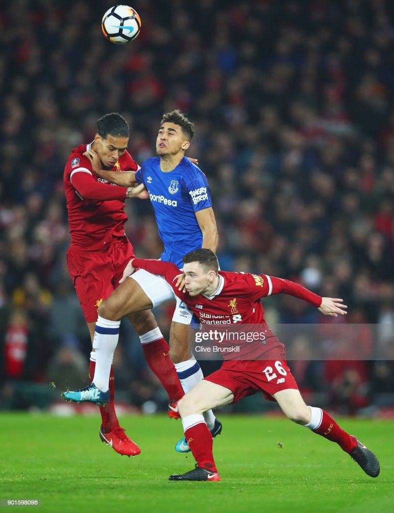 Dominic Calvert-Lewin of Everton jumps between Virgil van Dijk and Andy Robertson of Liverpool during the Emirates FA Cup Third Round match between Liverpool and Everton at Anfield on January 5, 2018 in Liverpool, England.