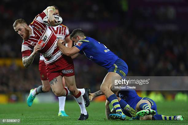 Dominic Crosby of Wigan is held up by Toby King of Warrington during the First Utility Super League Final between Warrington Wolves and Wigan...