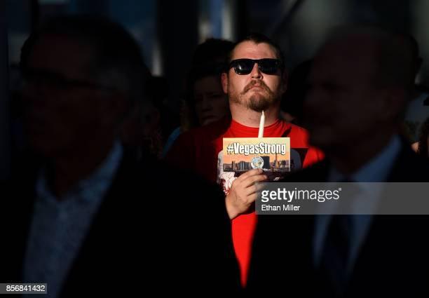 Dominic De Patta of Nevada holds a candle and a #VegasStrong flyer during a prayer vigil outside Las Vegas City Hall in response to Sunday's mass...