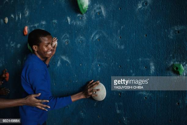 Dominic Hezron touches the artificial climbing wall during a weeklong free climbing training for visually impaired and blind students by the Japanese...