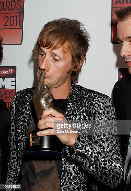 Dominic Howard of the band Muse poses with the 'Best British Band award supported by Shockwaves' in front of the winners boards at the Shockwaves NME...