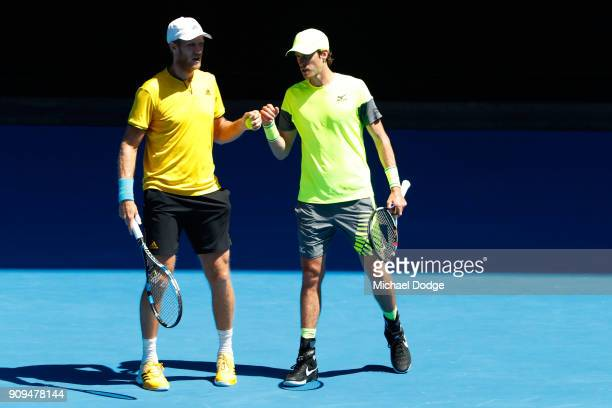 Dominic Inglot of Great Britain and Marcus Daniell of New Zealand talk tactics in their men's doubles quarterfinal match against Oliver Marach of...