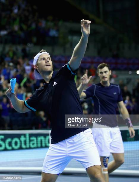 Dominic Inglot of Great Britain throws his wrist band to the crowd watched by his doubles partner Jamie Murray after they had celebrated match point...