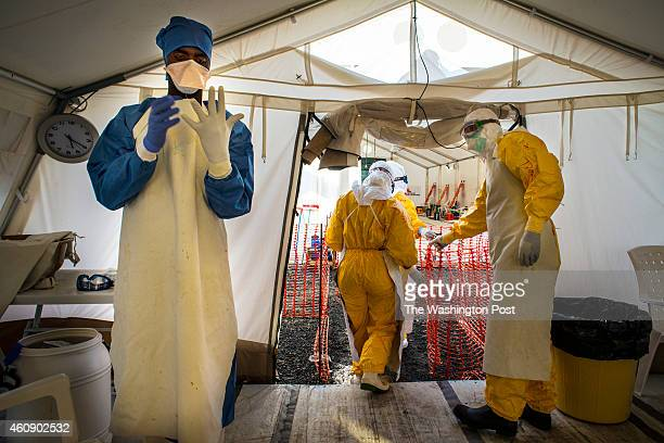 Dominic Kollie an Ebola survivor suits up to go inside an Ebola ward as other staff members move in ahead at the MSF ELWA3 Ebola Treatment Unit on...