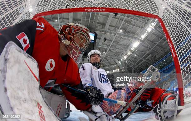 Dominic Larocque goaltender of Canada slides into the net with Joshua Misiwwicz of United States in the Ice Hockey gold medal game between Canada and...