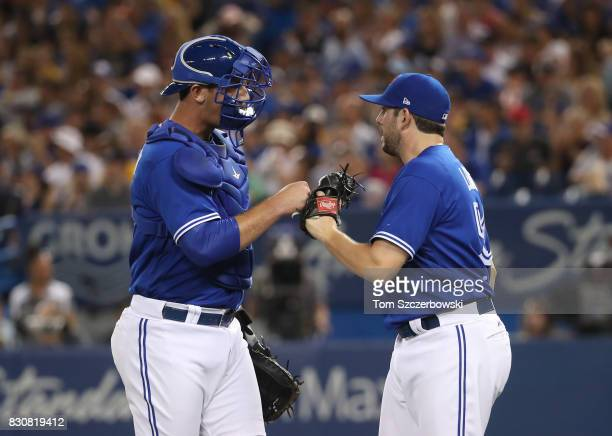 Dominic Leone of the Toronto Blue Jays celebrates with Mike Ohlman after getting the last out of the sixth inning during MLB game action against the...