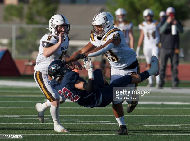 Dominic Martucci of the Herriman Mustangs is taken down by Ephraim Fiso and Caden Blackner of the Davis Darts at Mustang Stadium on August 13, 2020...