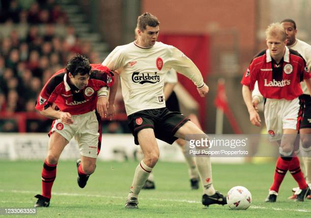 Dominic Matteo of Liverpool controls the ball under pressure from Dean Saunders of Nottingham Forest as teammate Alf-Inge Haaland looks on during an...