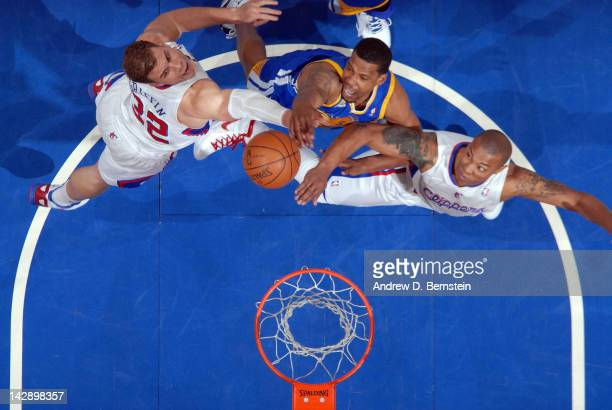 Dominic McGuire of the Golden State Warriors puts up a shot against Blake Griffin and Caron Buter of the Los Angeles Clippers at Staples Center on...