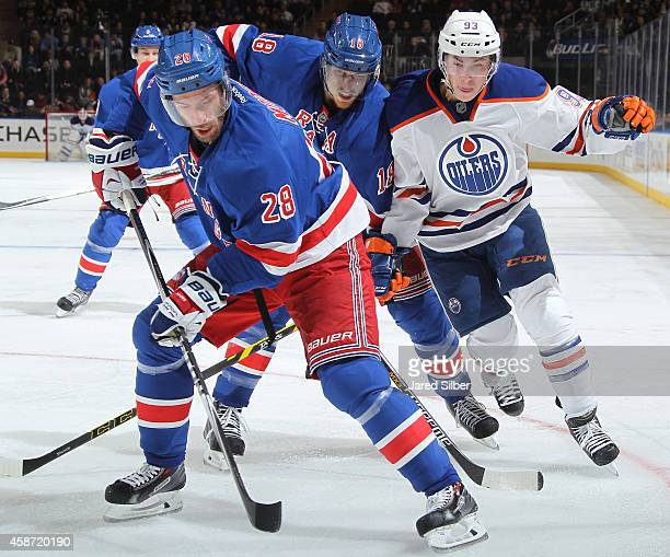 Dominic Moore and Marc Staal of the New York Rangers battle for the puck against Ryan NugentHopkins of the Edmonton Oilers at Madison Square Garden...