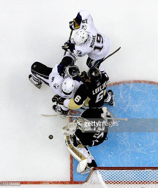 Dominic Moore and Ryan Malone of the Tampa Bay Lightning attempt to screen MarcAndre Fleury of the Pittsburgh Penguins as Ben Lovejoy defends in Game...