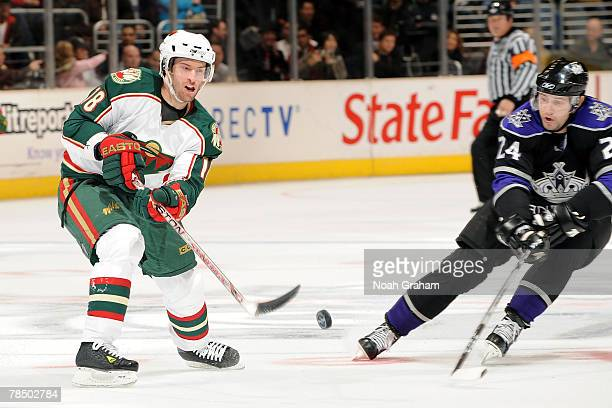 Dominic Moore of the Minnesota Wild shoots the puck against Alexander Frolov of the Los Angles Kings at Staples Center December 15 2007 in Los...