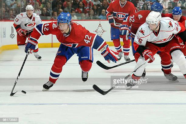 Dominic Moore of the Montreal Canadiens skates with the puck in front of Erik Cole of the Carolina Hurricanes during the NHL game on March 31 2010 at...