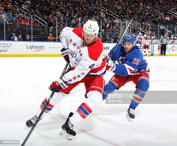 Dominic Moore of the New York Rangers and John Erskine of the Washington Capitals skate for the puck at Madison Square Garden on January 19 2014 in...