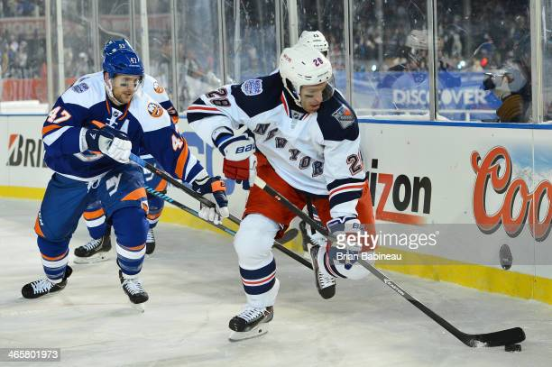 Dominic Moore of the New York Rangers controls the puck against Andrew MacDonald of the New York Islanders during the 2014 Coors Light NHL Stadium...