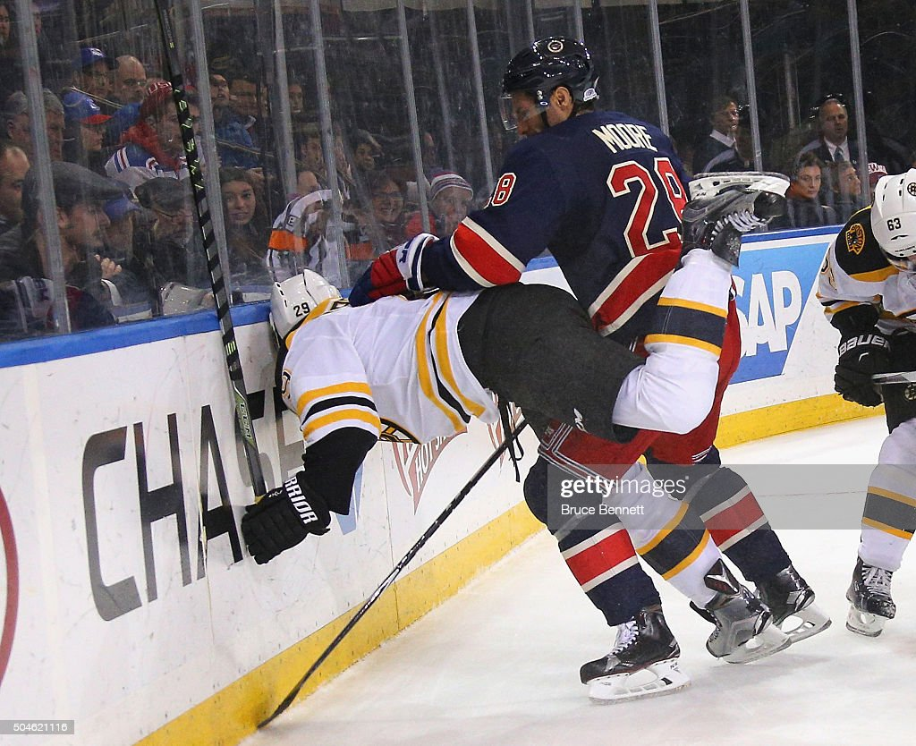 Dominic Moore #28 of the New York Rangers pushes Landon Ferraro #29 of the Boston Bruins into the boards during the third period at Madison Square Garden on January 11, 2016 in New York City. The Rangers defeated the Bruins 2-1.