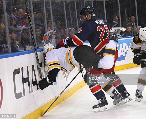 Dominic Moore of the New York Rangers pushes Landon Ferraro of the Boston Bruins into the boards during the third period at Madison Square Garden on...