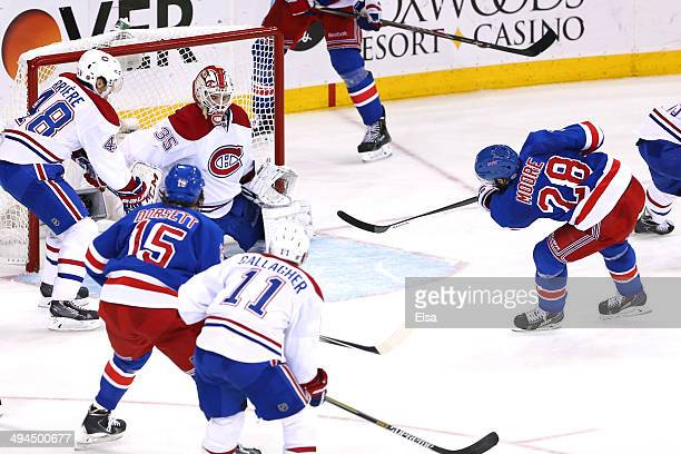 Dominic Moore of the New York Rangers scores a goal against Dustin Tokarski of the Montreal Canadiens in the second period during Game Six of the...